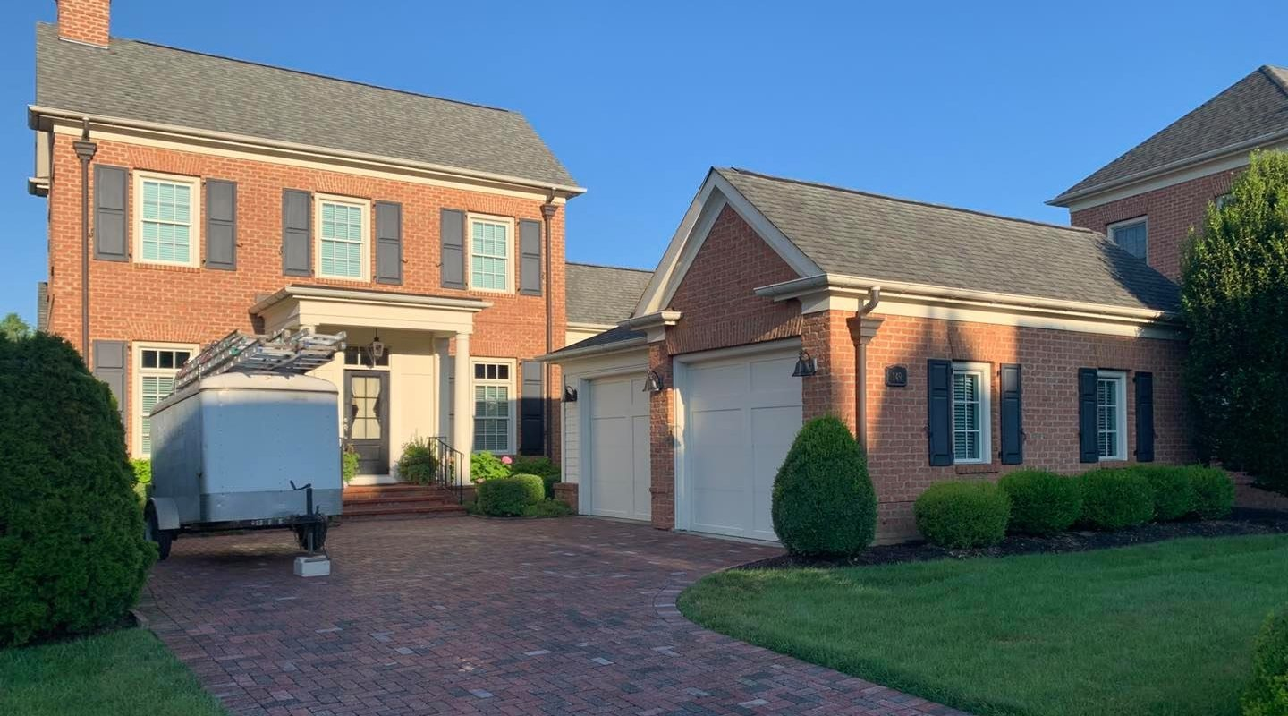 Brick House and Driveway with Sunlight Housepainting Trailer